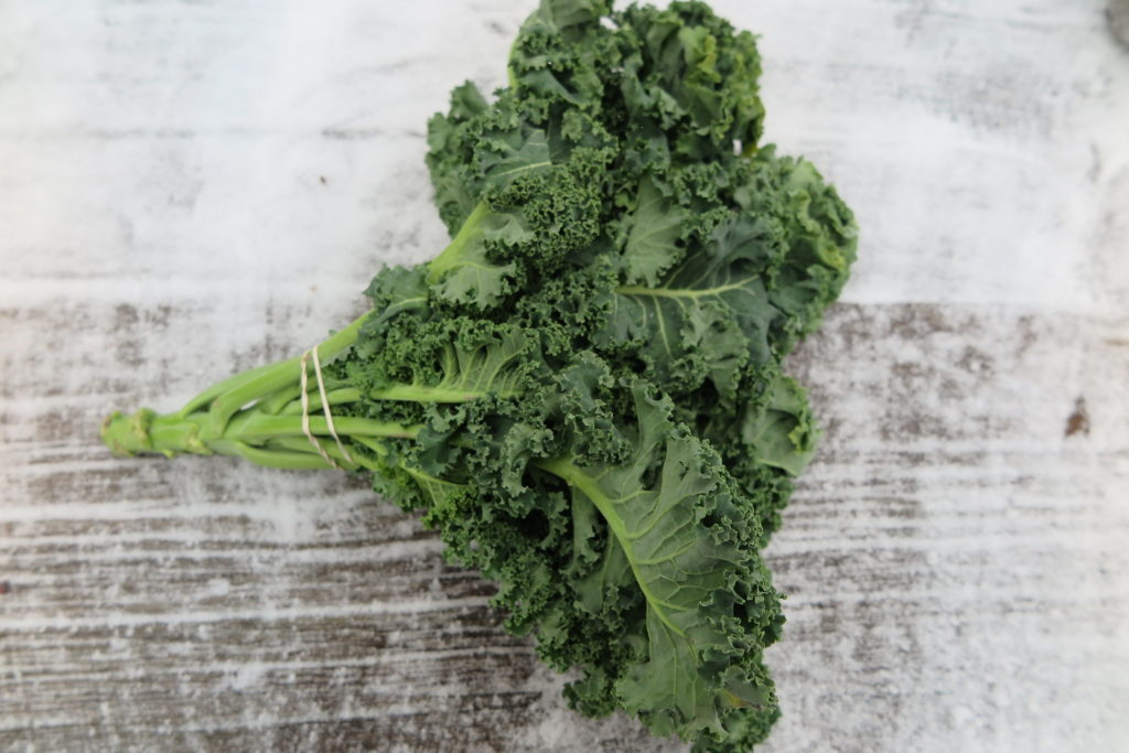 Bundle of leafy curly kale in a whitewashed wood background