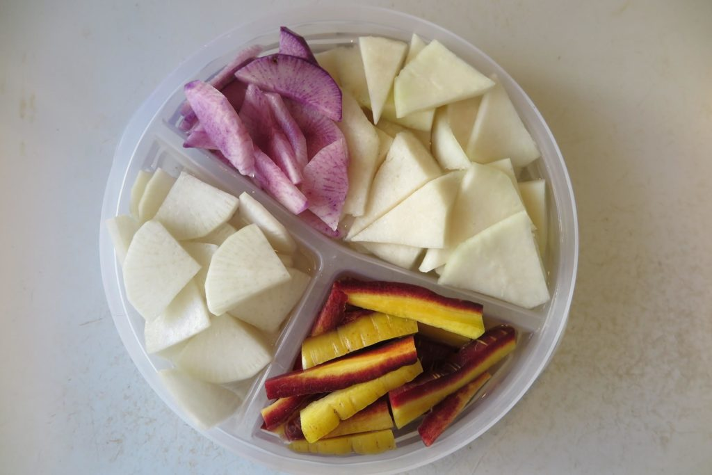 An overhead photo of a plate with four sections. Each section has slices of root vegetables cut into wedges