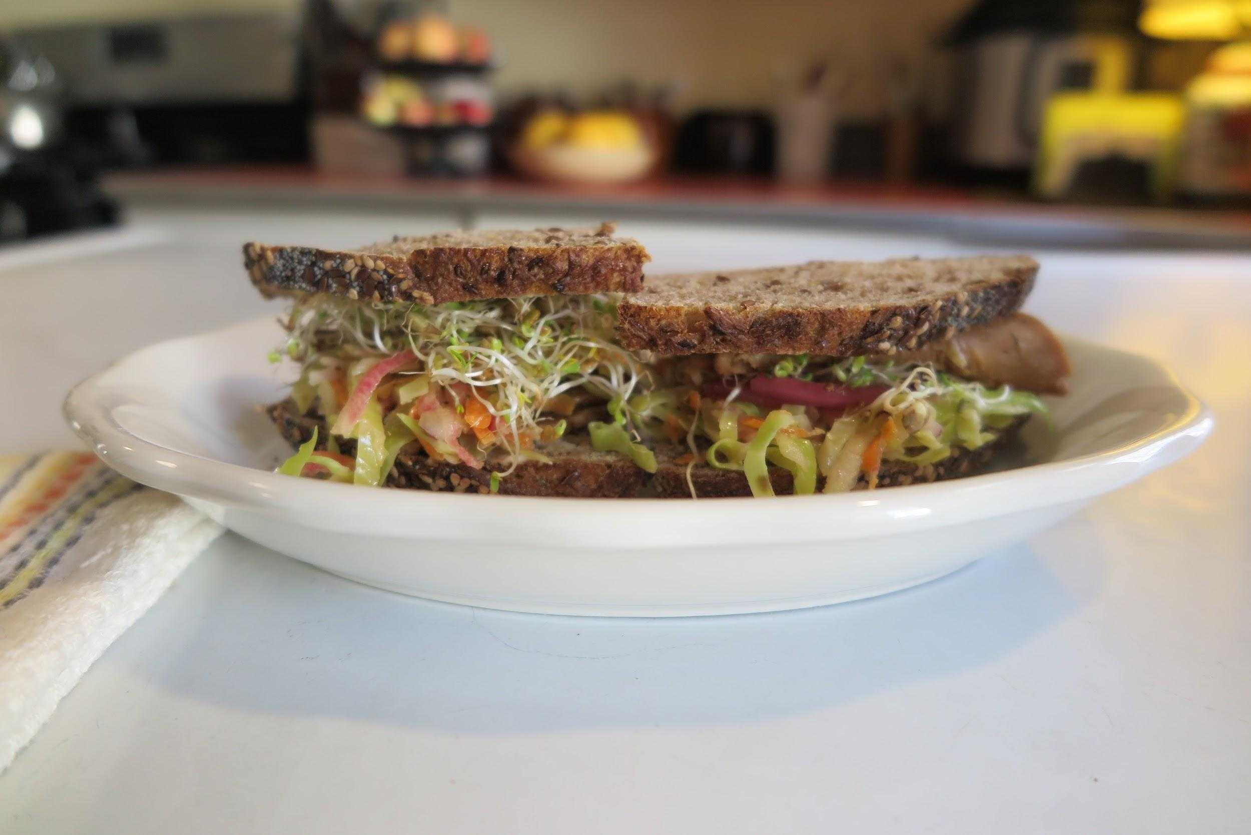 Profile shot of a sandwich with the coleslaw on a white plate.