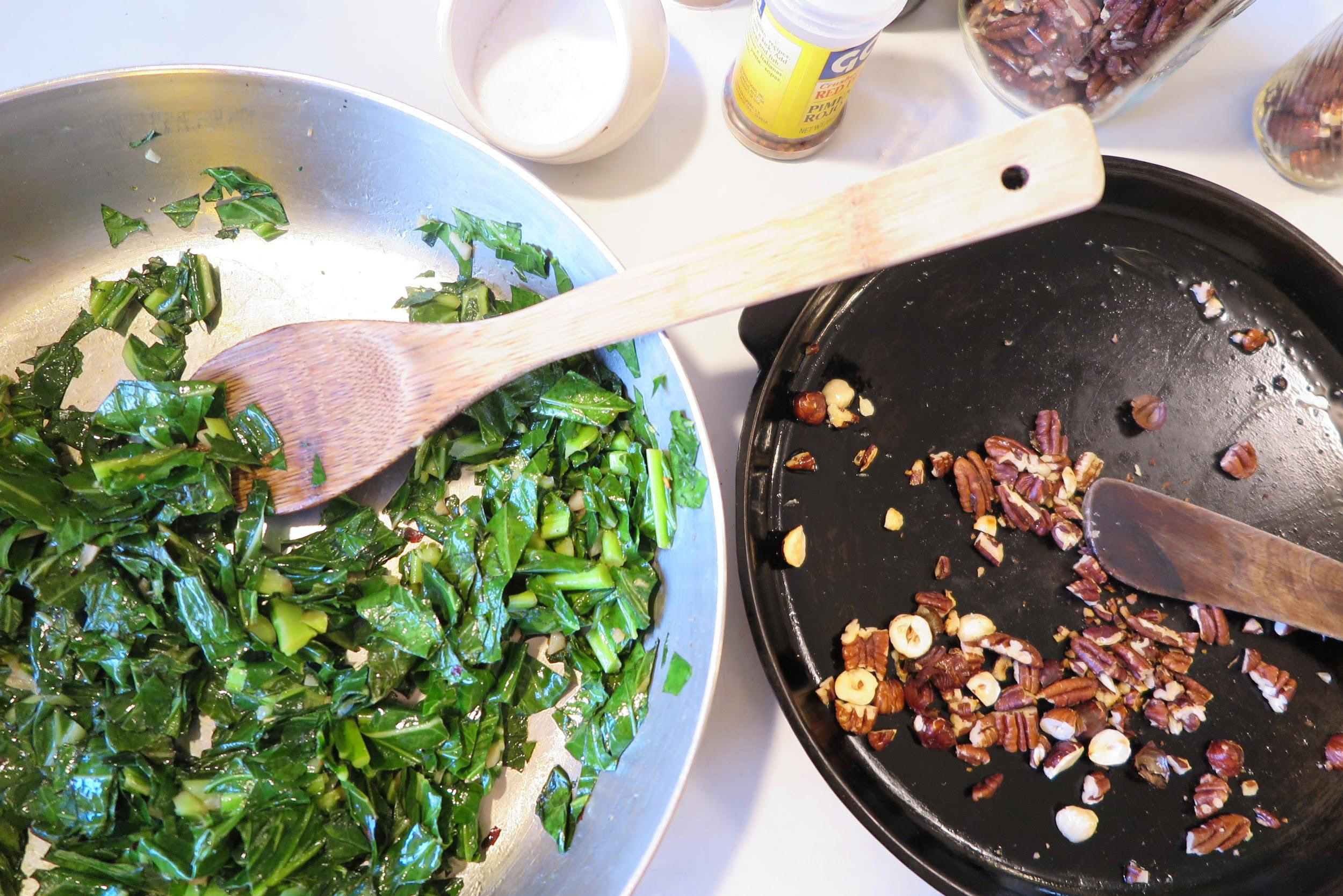 Silver sautee pan with leafy greens and a wooden spoon on the left. On the right, a cast iron pan with toasted chopped nuts.