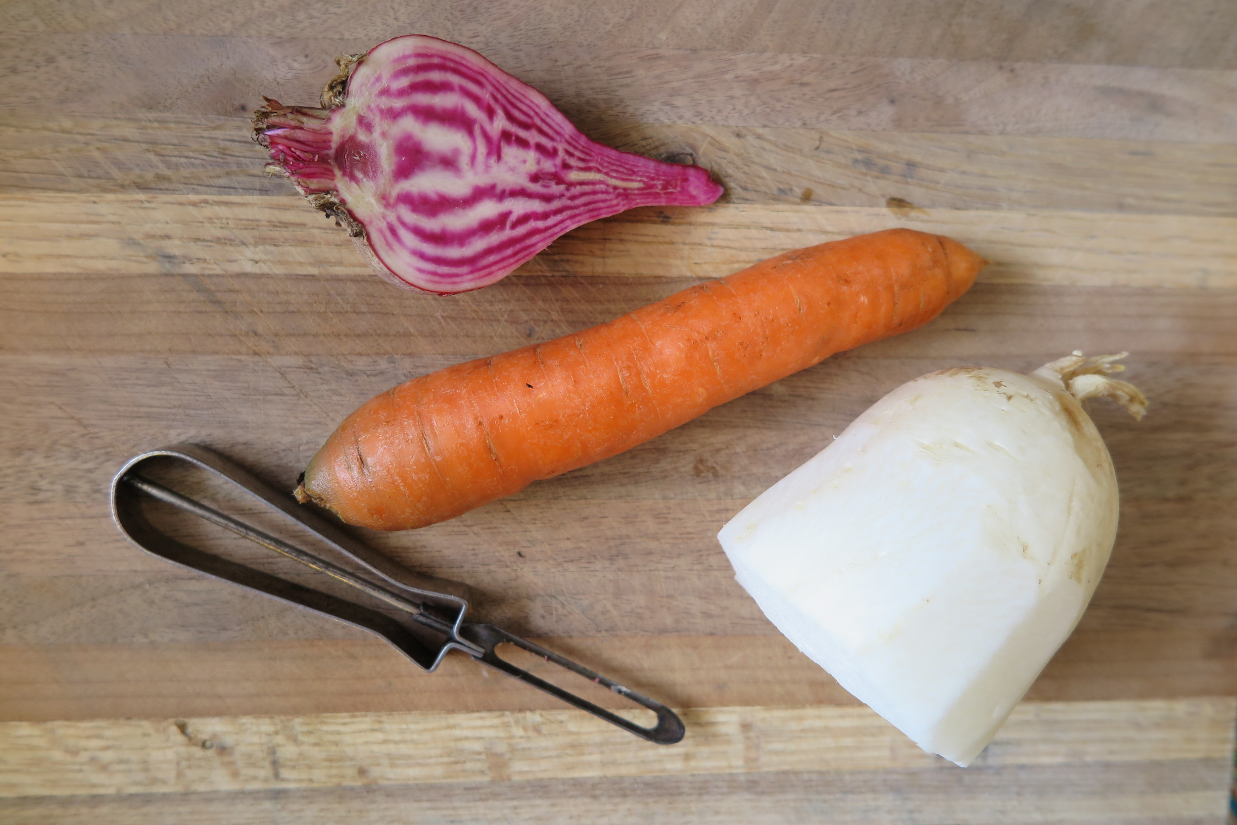 Two types of radishes and a carrot laying on a wooden cutting board ready to be peeled and chopped