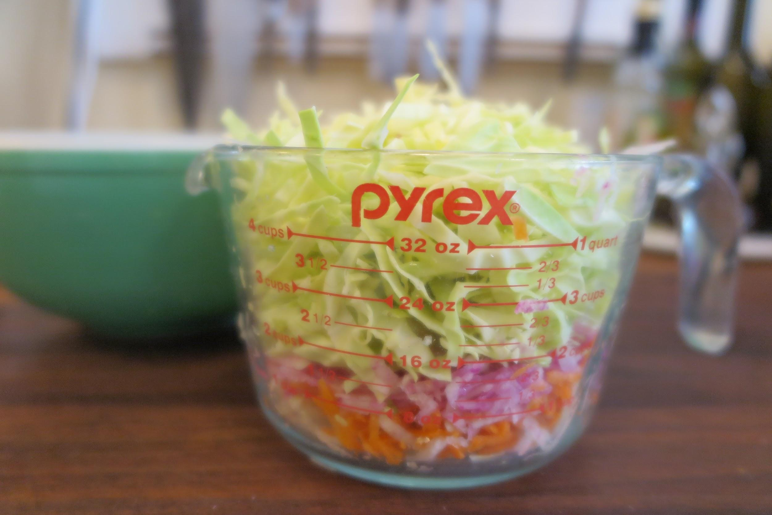 A large glass Pyrex measuring cup filled with shredded cabbage, radishes, and carrots