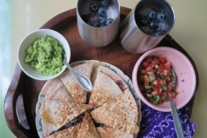 Quesadillo on a wood tray with small bowls of guacamole, pico de gallo, and two glasses of ice water with blueberries