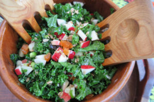 Wood salad bowl with salad forks, filled with small pieces of curly kale, apples, and farro