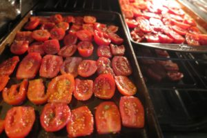 slices of roma tomatoes on cookie sheets in the oven